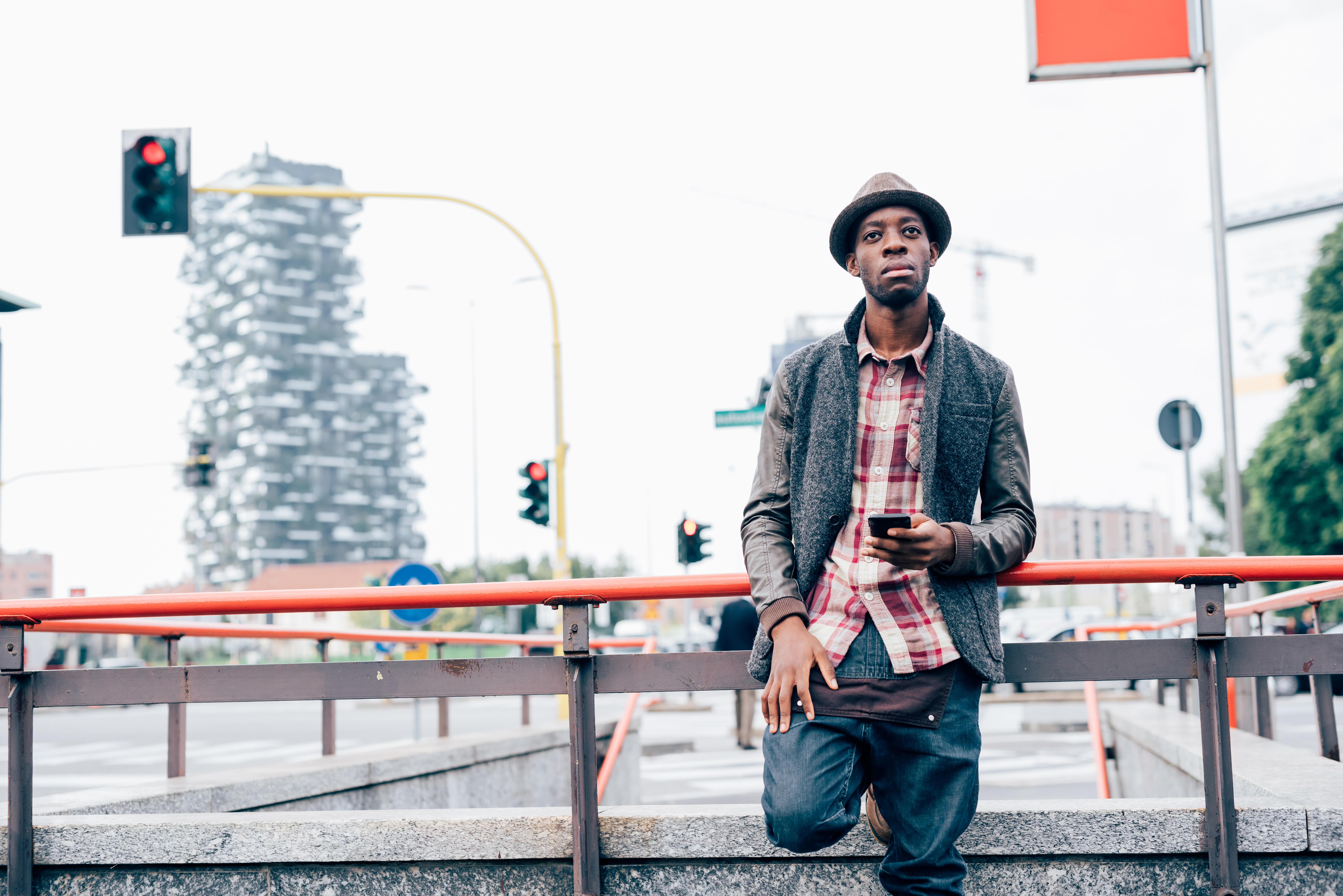 Knee figure of young handsome afro black man leaning on a handrail, holding a smart phone, looking over pensive- technology, social network, communication concept